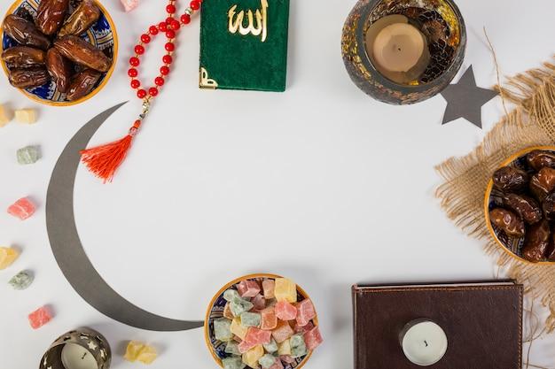 Datteri di palma succosi freschi; rosari; candela; luna crescente; santo kuran con spazio su sfondo bianco