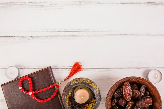 Datteri di palma succosi freschi sulla ciotola con perline di preghiera; candele accese sulla scrivania in legno bianco