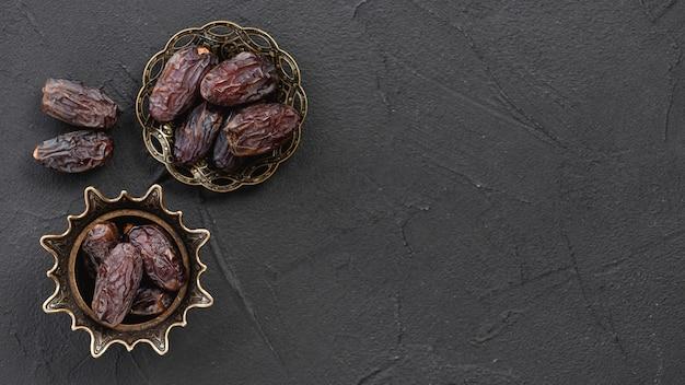 Datteri dolci di frutta secca nella ciotola di metallo elegante in rame sulla superficie nera