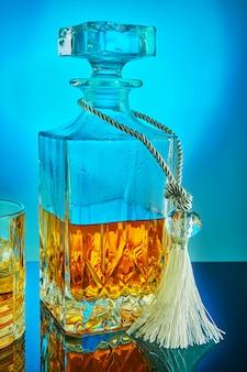 Decanter di cristallo quadrato con whisky scozzese o brandy su uno sfondo blu sfumato con la riflessione