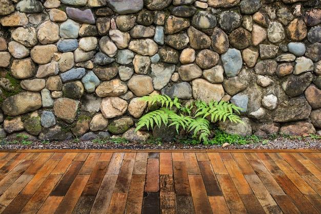Decking in legno con sfondo muro di pietra.