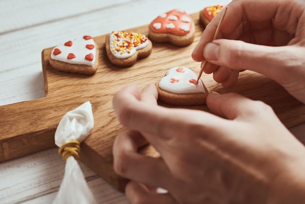 Decorare i biscotti di pan di zenzero con glassa. le mani della donna decorano i biscotti nella forma di cuore, primo piano
