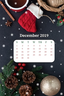 Decorare in granito nero con calza rossa, pallina di gingillo, foglia di pino e coni, cioccolata calda, neve e decorazioni festive