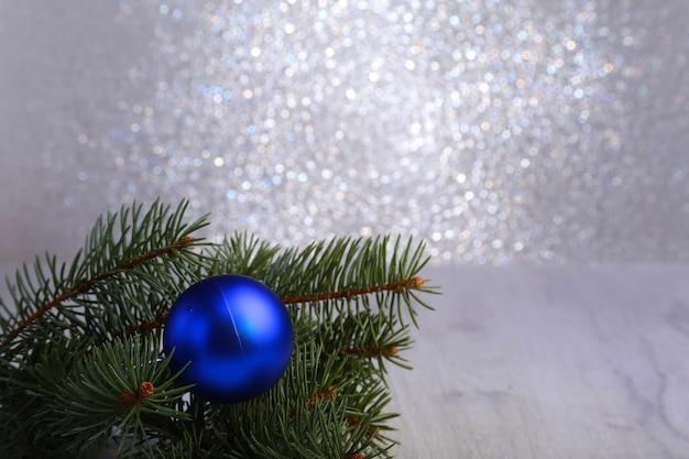 Decorativo con rami di abete e palline blu sull'argento. cartolina di natale concetto di vacanza
