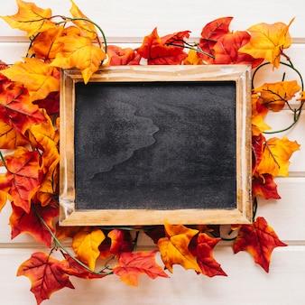 Decorazione autunnale con ardesia su foglie d'autunno