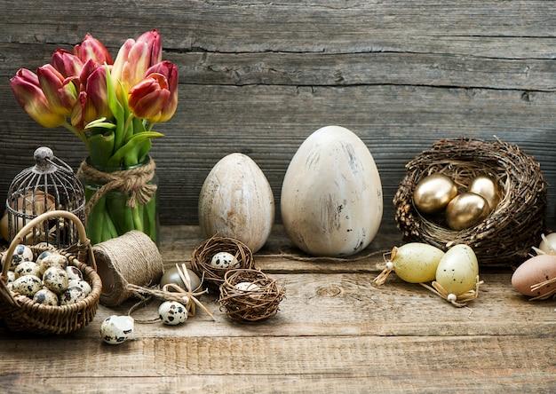 Decorazione d'annata di pasqua con le uova ed i fiori rossi del tulipano