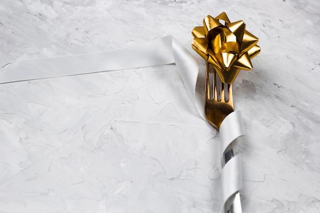 Decorazione da tavola per una cena, forchetta d'oro con nastro di raso bianco lucido