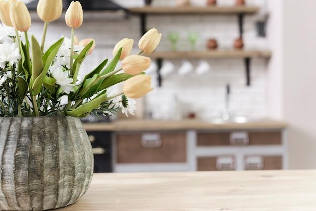 Decorazione del fiore del primo piano sul ripiano del tavolo in cucina moderna