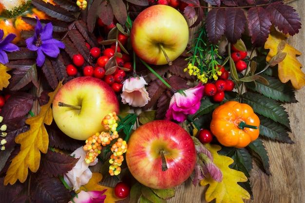 Decorazione del ringraziamento con foglie di sorbo, mele, fiori rosa e viola, vista dall'alto
