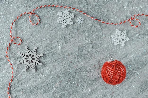 Decorazione dell'albero di natale fatta della palla rossa del filato e fiocchi di neve di legno bianchi su fondo d'argento