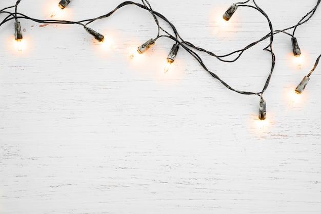 Decorazione della lampadina delle luci di natale su legno bianco. sfondo di vacanze di natale e capodanno. vista dall'alto