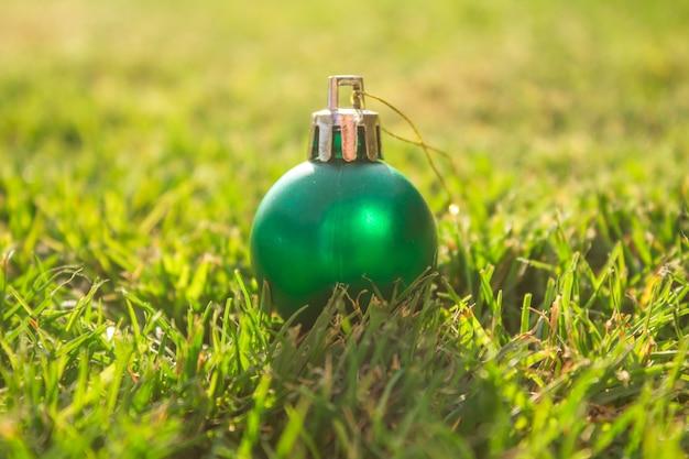 Decorazione della palla verde di natale su erba. boke sfondo.