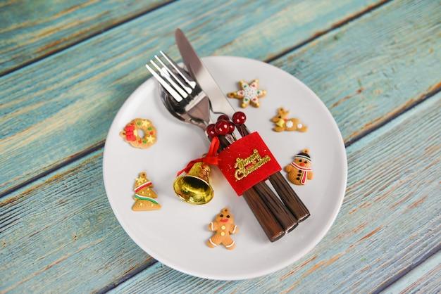 Decorazione della regolazione di posto della tavola di natale con il cucchiaio e il coltello della forcella sul tavolo da pranzo di legno del piatto bianco