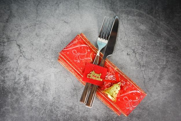 Decorazione della regolazione di posto della tavola di natale con il cucchiaio e il coltello della forcella sul tovagliolo sulla tavola