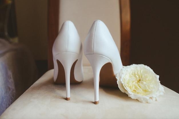 Decorazione della scarpa della donna e delle rose bianche, scarpa della ragazza con il fiore tenero dentro la foto di arti