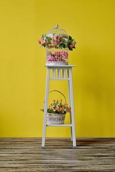 Decorazione della stanza con gabbia per uccelli e cestino con i fiori