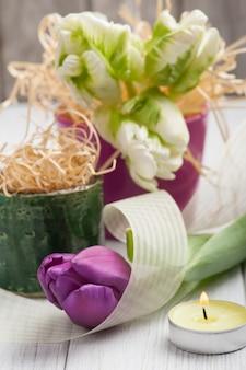 Decorazione della tavola di primavera con tulipani e candela accesa
