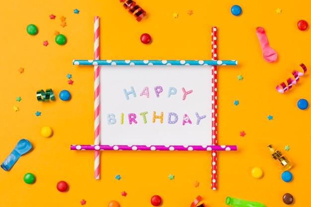 Decorazione di buon compleanno con streamer; palloncino; gemme e granelli su sfondo giallo