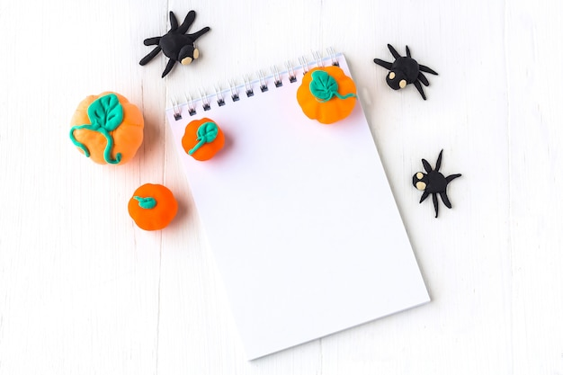 Decorazione di halloween: zucche e ragni fatti a mano da plasticin e taccuino con spazio per testo su un fondo di legno bianco.