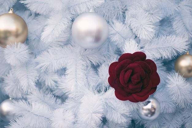 Decorazione di natale bianco con le sfere rosse e sfere d'argento sull'albero di natale