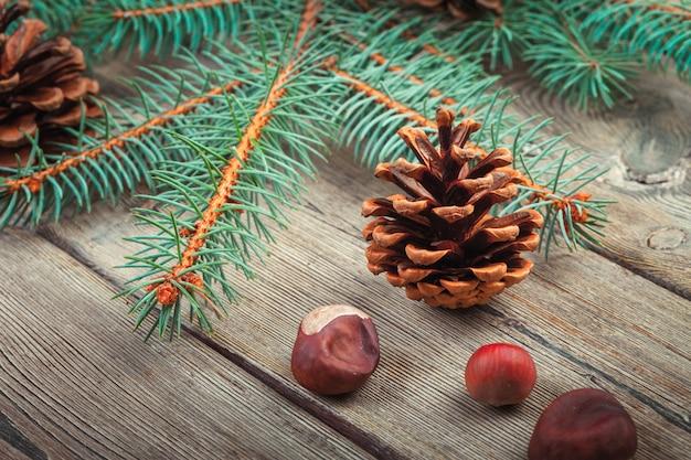 Decorazione di natale con l'albero di abete e pigne su legno bianco