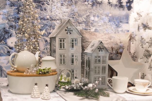 Decorazione di natale con la casa del candeliere di natale sulla tabella sopra le luci vaghe