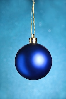 Decorazione di natale con la sfera blu su priorità bassa blu con i fiocchi di neve che cadono dal cielo. composizione di buone feste.