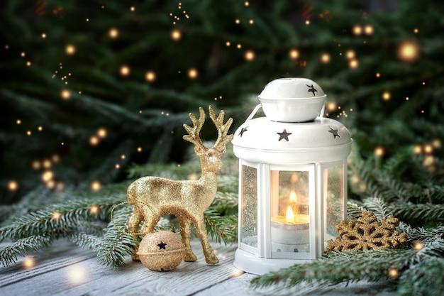 Decorazione di natale con lanterna, fiocco di neve d'oro e palle, rami di abete e ornamenti su sfondo scuro.