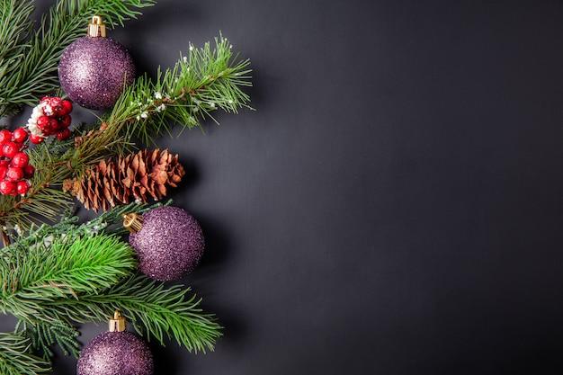 Decorazione di natale sfondo nero con palle di natale e pini