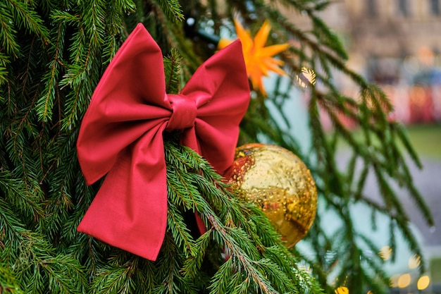 Decorazione di natale sotto forma di un arco rosso con una sfera gialla su un albero di natale verde