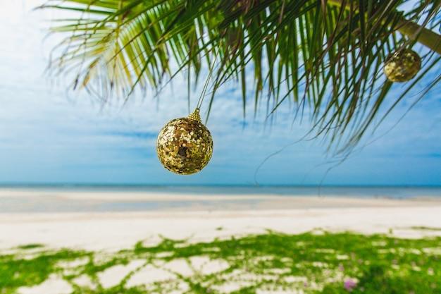 Decorazione di natale sulla palma sulla spiaggia il giorno soleggiato