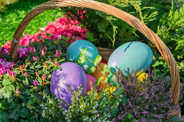 Decorazione di strada di pasqua. cesto di vimini pieno di uova di pasqua dipinte, torta e fiori.