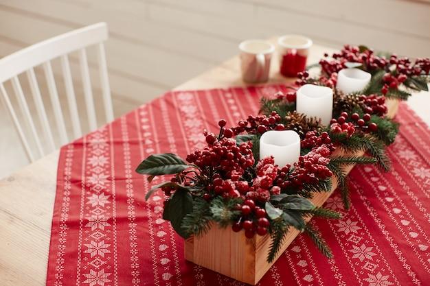 Decorazione di vacanze invernali preparativi in studio piatto in legno con bacche rosse e fiori