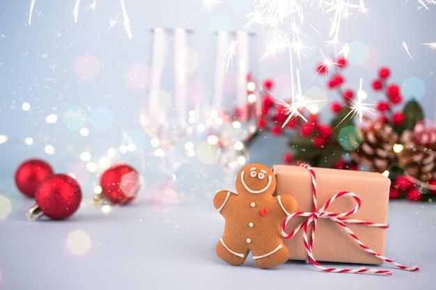 Decorazione festiva con regalo, omino di pan di zenzero, decorazioni natalizie e bicchieri per champagne