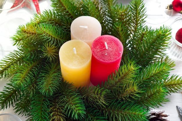 Decorazione festiva sulla tavola di natale con candele, lanterna, stoviglie e vino gl