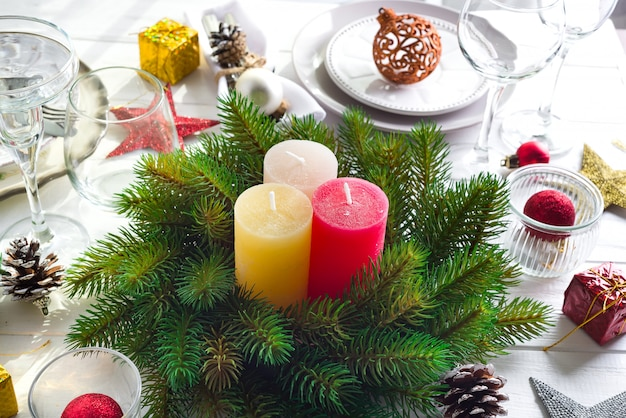 Decorazione festiva sulla tavola di natale con candele, lanterne, stoviglie
