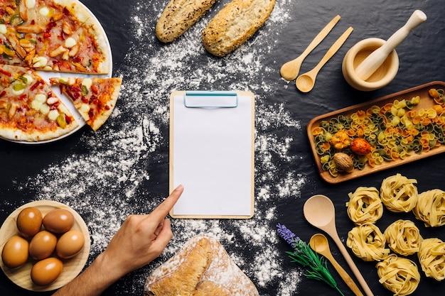 Decorazione italiana di cibo con dito che punta su appunti