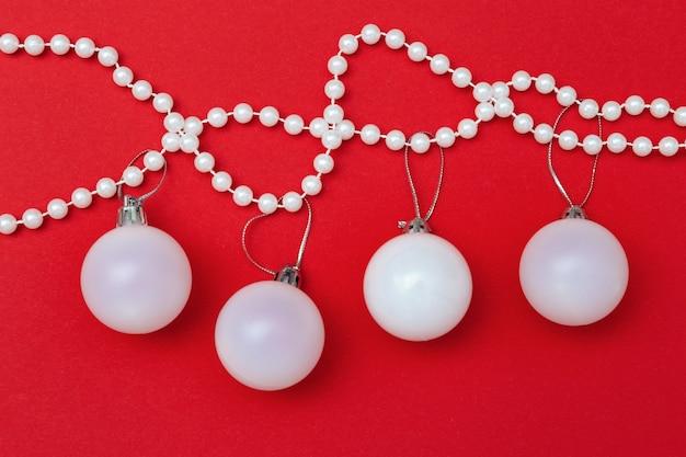 Decorazione natalizia, bella palla bianca da vicino consegna su perle su rosso