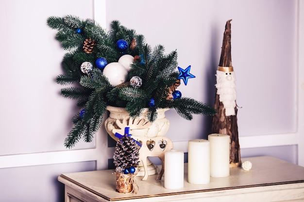 Decorazione natalizia in vaso e accanto a candela, cervo, babbo natale in legno.