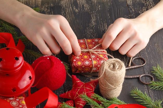 Decorazione natalizia. la vista superiore delle mani del bambino avvolge il presente di nuovo anno. regali e pergamene confezionati, rami di abete e strumenti sul tavolo di legno squallido.