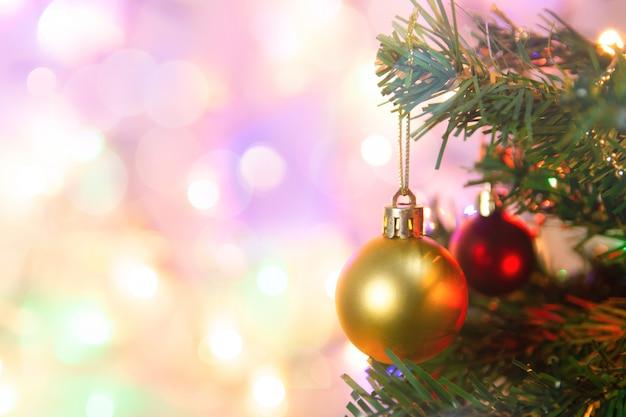 Decorazione natalizia. palle d'attaccatura dell'oro sulla ghirlanda e sugli ornamenti dell'albero di natale dei rami del pino sopra bokeh astratto con lo spazio della copia
