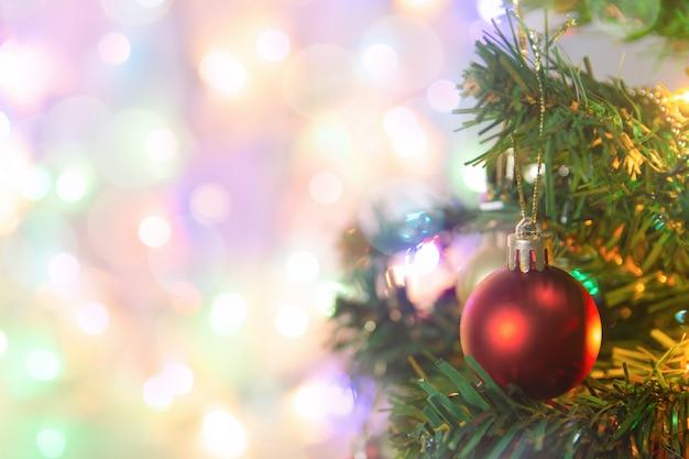 Decorazione natalizia. palle rosse d'attaccatura sulla ghirlanda e sugli ornamenti dell'albero di natale dei rami del pino sopra bokeh astratto con lo spazio della copia