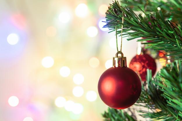 Decorazione natalizia. palle rosse d'attaccatura sulla ghirlanda e sugli ornamenti dell'albero di natale dei rami del pino sopra il fondo astratto del bokeh con copyspace