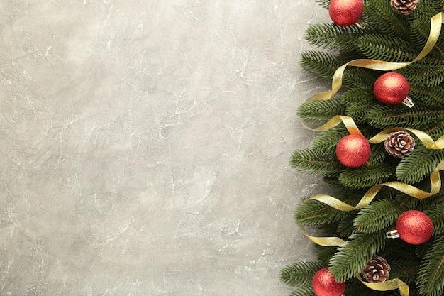 Decorazione natalizia. ramo dell'abete con le palle e il nastro dell'oro su fondo concreto grigio
