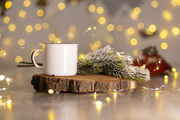 Decorazione per le vacanze di capodanno, calda atmosfera accogliente, tazza di metallo bianco su un supporto di legno, accanto a un ramo di albero di natale innevato,