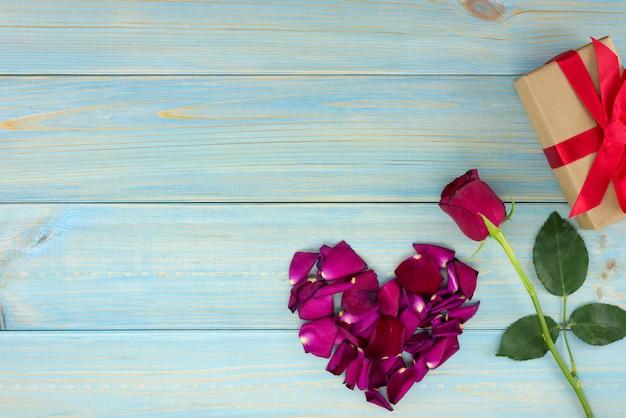 Decorazione romantica di giorno di biglietti di s. valentino con le rose e la scatola del gif su una tavola di legno blu.