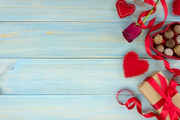 Decorazione romantica di giorno di san valentino con rose e cioccolato su un tavolo di legno blu.