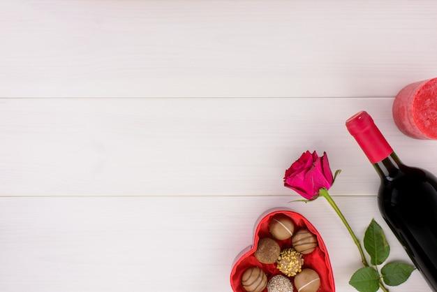Decorazione romantica di giorno di san valentino con rose, vino e cioccolato su un tavolo di legno bianco.