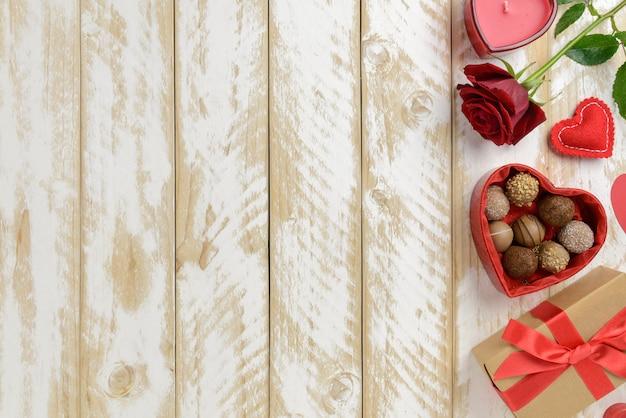Decorazione romantica di san valentino con rose e cioccolato su un tavolo di legno bianco. vista dall'alto, copia spazio.