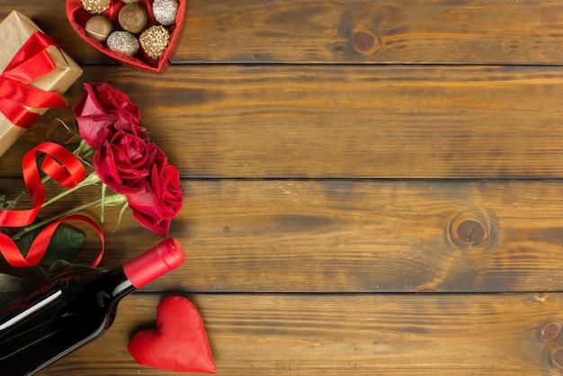Decorazione romantica di san valentino con rose, vino e cioccolato su un tavolo in legno marrone